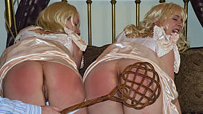 Both spankbots receive the carpet beater across their lifelike butts
